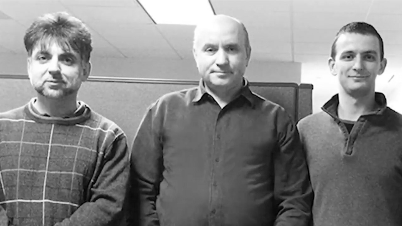Black and white pick of Mark and other PCMI employees in office