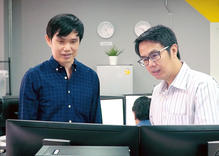 Thailand team members looking at computer screen